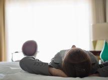 Femme d'affaires s'étendant sur le bâti dans la chambre d'hôtel Photos libres de droits