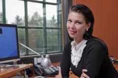 Femme d'affaires s'asseyant à l'ordinateur à son bureau Images stock