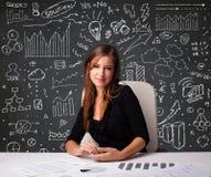 Femme d'affaires s'asseyant au bureau avec le plan et les icônes d'affaires Photographie stock libre de droits