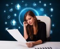 Femme d'affaires s'asseyant au bureau avec les graphismes sociaux de réseau Images stock