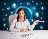 Femme d'affaires s'asseyant au bureau avec les graphismes sociaux de réseau Photographie stock