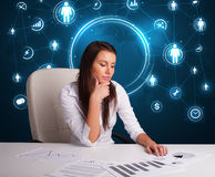 Femme d'affaires s'asseyant au bureau avec les graphismes sociaux de réseau Photo stock