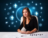 Femme d'affaires s'asseyant au bureau avec les graphismes sociaux de réseau Photos stock