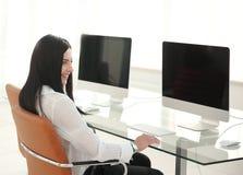 Femme d'affaires s'asseyant au bureau dans le bureau moderne Image libre de droits