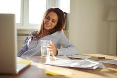 Femme d'affaires s'asseyant au bureau dans son siège social Image stock