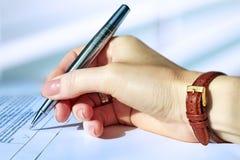 Femme d'affaires s'asseyant au bureau signant un contrat par le stylo Photos libres de droits