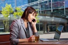 Femme d'affaires s'asseyant au café extérieur avec l'ordinateur portable Photo stock