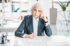 Femme d'affaires s'asseyant au lieu de travail et au contrat de signature Images stock