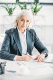 Femme d'affaires s'asseyant au lieu de travail et au contrat de signature Photos stock