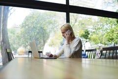 Femme d'affaires s'asseyant dans l'intérieur de bureau ou le sho moderne de café Photos stock