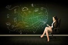Femme d'affaires s'asseyant dans la chaise tenant le comprimé avec des icônes de media Images libres de droits