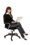 Femme d'affaires s'asseyant dans la présidence de bureau avec l'ordinateur portatif photographie stock libre de droits