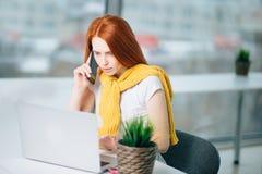 Femme d'affaires s'asseyant dans le bureau au bureau, regardant l'ordinateur portable et le smartphone d'utilisations Image stock