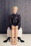 Femme d'affaires s'asseyant dans le procès noir Image stock