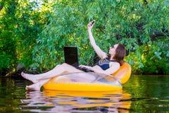 Femme d'affaires s'asseyant dans un anneau gonflable dans un espace de rivière Photos stock