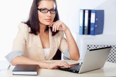 Femme d'affaires s'asseyant derrière le bureau Photographie stock