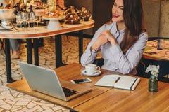 Femme d'affaires s'asseyant en café à la table et à rire Sur le bureau est l'ordinateur portable, carnet, smartphone Travail de d photo libre de droits