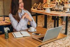 Femme d'affaires s'asseyant en café à la table et à rire Sur le bureau est l'ordinateur portable, carnet, smartphone Travail de d photo stock