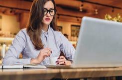 Femme d'affaires s'asseyant en café à la table et à rire Sur le bureau est l'ordinateur portable, carnet, smartphone Travail de d photographie stock