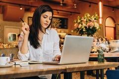 Femme d'affaires s'asseyant en café à la table, regardant sur l'écran de l'ordinateur, souriant Travail de distance Marketing en  Images libres de droits