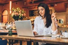 Femme d'affaires s'asseyant en café à la table, regardant sur l'écran de l'ordinateur, souriant Travail de distance Marketing en  Image libre de droits