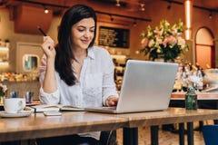 Femme d'affaires s'asseyant en café à la table, regardant sur l'écran de l'ordinateur, souriant Travail de distance Marketing en  photographie stock libre de droits