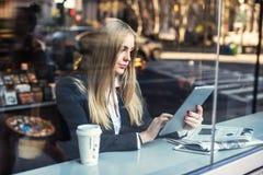 Femme d'affaires s'asseyant en café et à l'aide du PC de comprimé et café potable image libre de droits