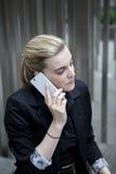 Femme d'affaires s'asseyant et parlant au téléphone Photographie stock libre de droits