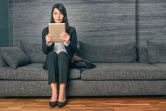 Femme d'affaires s'asseyant lisant un Tablette-PC Photographie stock