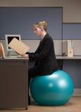Femme d'affaires s'asseyant sur la bille d'exercice Image libre de droits