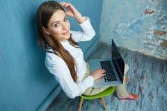 Femme d'affaires s'asseyant sur la chaise avec l'ordinateur portable dans la chambre de vintage Photographie stock