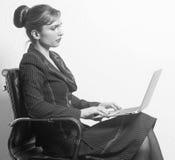 Femme d'affaires s'asseyant sur la chaise avec le carnet dans le bureau images stock