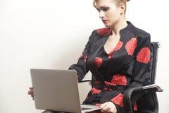 Femme d'affaires s'asseyant sur la chaise avec le carnet i photo stock