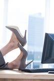 Femme d'affaires s'asseyant sur la chaise pivotante avec des pieds sur le bureau Images libres de droits