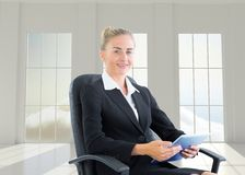 Femme d'affaires s'asseyant sur la chaise pivotante avec le comprimé Photo stock