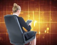 Femme d'affaires s'asseyant sur la chaise pivotante avec le comprimé Photographie stock libre de droits