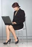 Femme d'affaires s'asseyant sur la présidence avec l'ordinateur portatif Photographie stock libre de droits