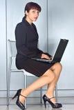 Femme d'affaires s'asseyant sur la présidence avec l'ordinateur portatif Photo stock