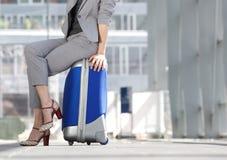 Femme d'affaires s'asseyant sur la valise à l'aéroport Images libres de droits
