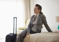 Femme d'affaires s'asseyant sur le bâti dans la chambre d'hôtel Image stock