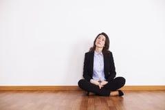 Femme d'affaires s'asseyant sur le plancher Photo stock