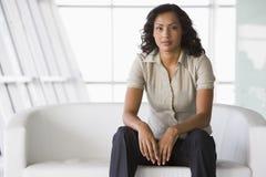 Femme d'affaires s'asseyant sur le sofa dans l'entrée Image stock