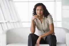 Femme d'affaires s'asseyant sur le sofa dans l'entrée Photographie stock