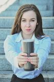 Femme d'affaires s'asseyant sur les étapes pendant la pause de midi, et les offres pour boire une tasse chaude image libre de droits