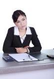Femme d'affaires s'asseyant sur son bureau et pensant avec les documents s Image stock