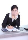 Femme d'affaires s'asseyant sur son bureau et pensant avec les documents s Images stock