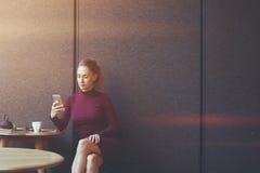 Femme d'affaires sûre à l'aide de son téléphone intelligent tout en détendant après jour de travail dans le café Photos libres de droits
