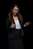 Femme d'affaires sûre de brune tenant le smartphone et montrant le pouce  Photos libres de droits
