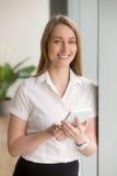 Femme d'affaires sûre de sourire tenant le comprimé numérique regardant a image stock