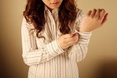 Femme d'affaires se boutonnant vers le haut de sa chemise Image stock